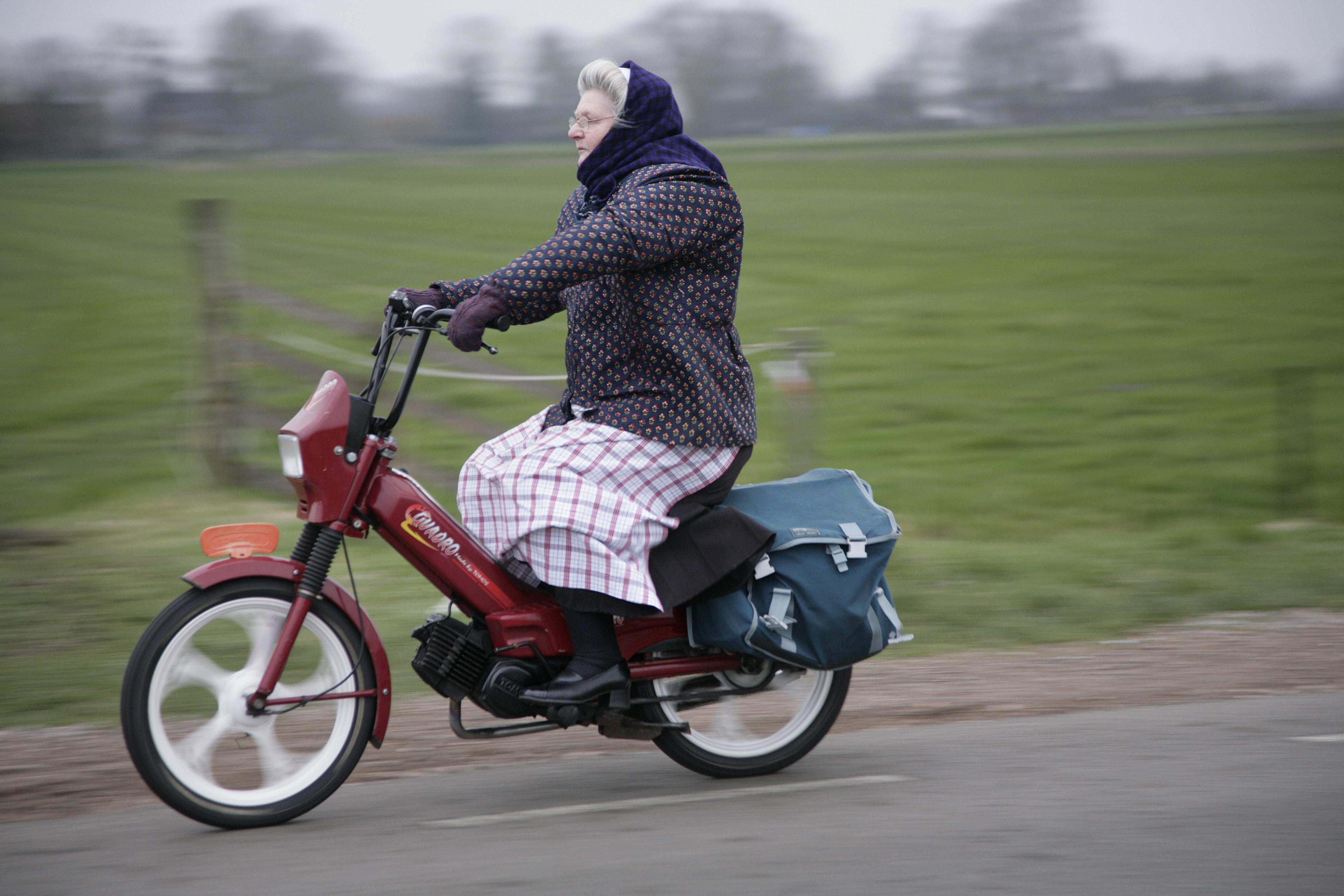 Vrouw in Spakenburger streekdracht, met hulk of grootjak, op de brommer. Foto: Bert Verhoeff.