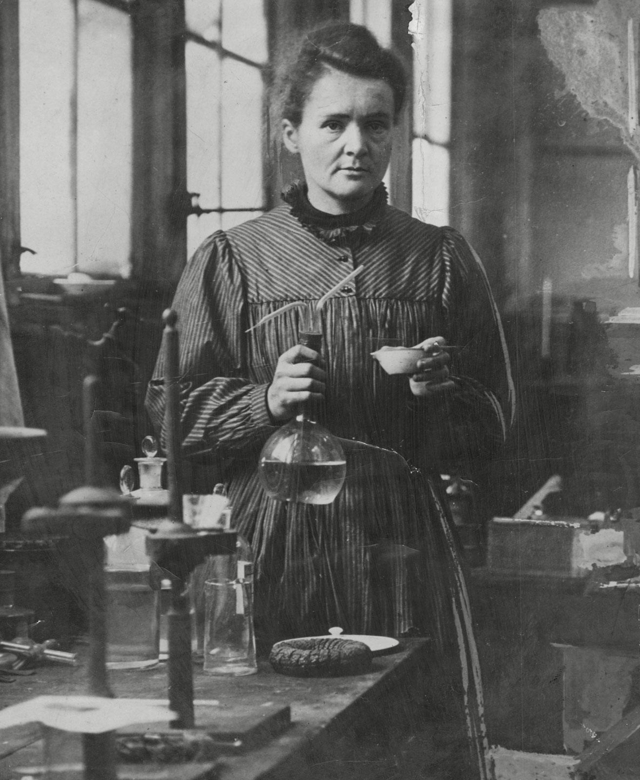 Marie Curie (1867-1934) in haar laboratorium, radioactieve mode uit de geschiedenis, museum, Amsterdam Museum geschreven door Marit Eisses voor Modemuze. Marie Curie, radium, 20e eeuw,  reclamemateriaal voor radioactieve producten, mode, radioactieve mode