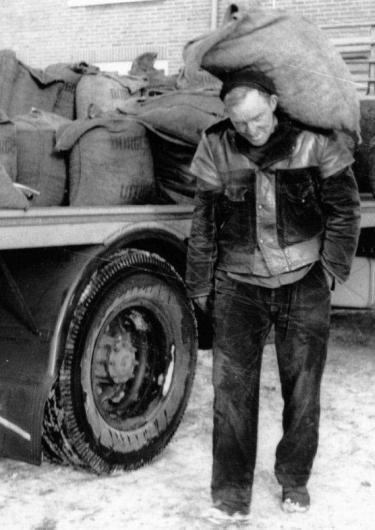 Man met werkkleding aan met zak op rug, Een kolensjouwer in Groningen in 1963 met een broek en een jas van ijzersterk manchester. Foto (uitsnede): Fotobedrijf Piet Boonstra, www.beeldbankgroningen.nl
