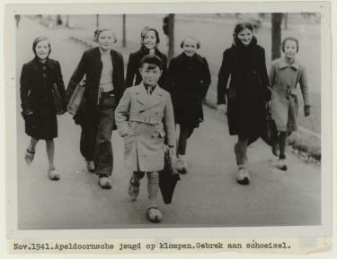 Lachend groepje kinderen op klompen onderweg naar school. Voorop een jongen met een alpionopet. Achter hem lopen zes meisjes. Twee dragen een hoofddoek. Allen hebben schooltassen. Onderaan de foto een getypte tekst.