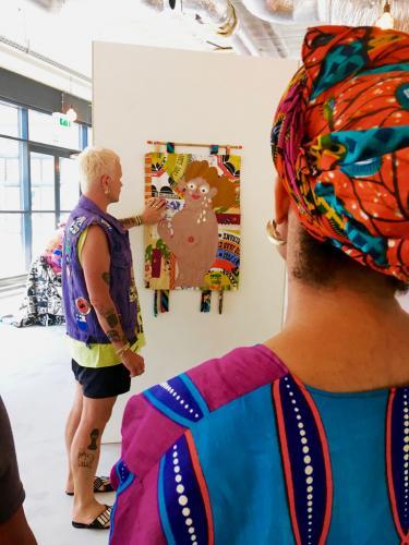 Bas Koster tijdens een rondleiding in de tentoonstelling 'Tranen zijn de glitters van het leven'. In deze serie wandkleden maakte Bas gebruik van stoffen voor speciale gelegenheden. Foto: Sabine Bolk