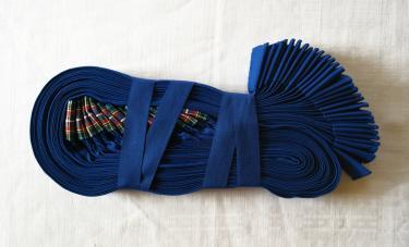 Opgevouwen werkschort, van blauw terlenka met een zogenoemd 'boordje' (tailleband) van geruite polyester.