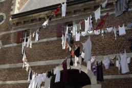 Ondergoed hangt aan waslijnen kris kras door elkaar tussen kasteelmuren