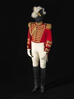 Rode jas, witte broek en zwarte knielaarzen.