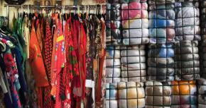 Vintagekleding en balen met tweedehands, gedoneerde kleding, klaar om gesorteerd te worden.