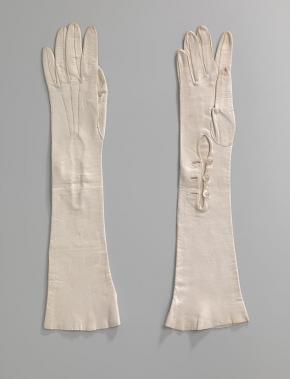 Paar lange dameshandschoenen van wit glacéleer. Op de hand drie stiksels. Bij de pols sluitend middels drie witte kunststof knopen. Amsterdam Museum (objectnummer KA 17210).