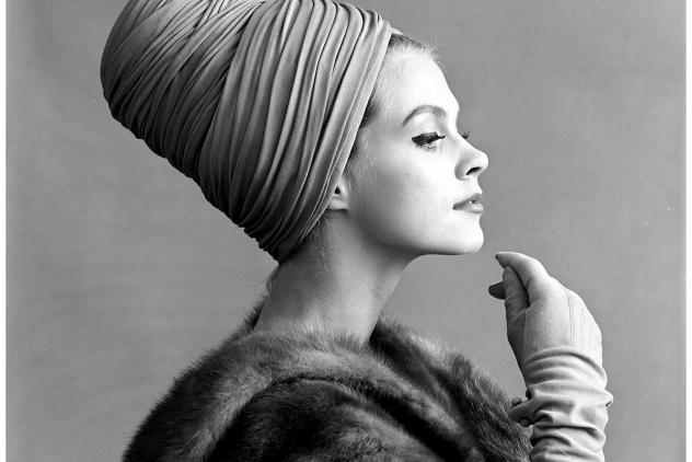 Zwart-wit foto. Mannequin Bonny Huf draagt op deze foto een tulband van dunne abrikooskleurige zijden jersey, die Max Heymans in 1961 ontwierp voor modehuis Hirsch.