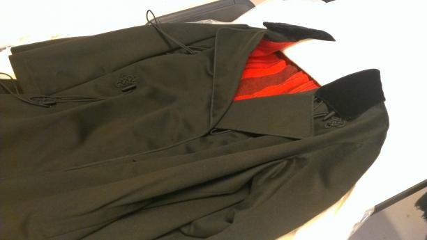Detailfoto avondmantel. De knal rode voering steekt fel af tegen zwart-groene stof van de buitenkant.