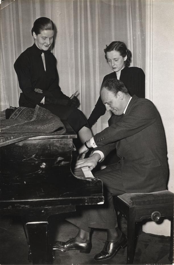 Pierre Balmain in Amsterdam achter de piano, vergezeld door twee medewerkers van Goyaarts
