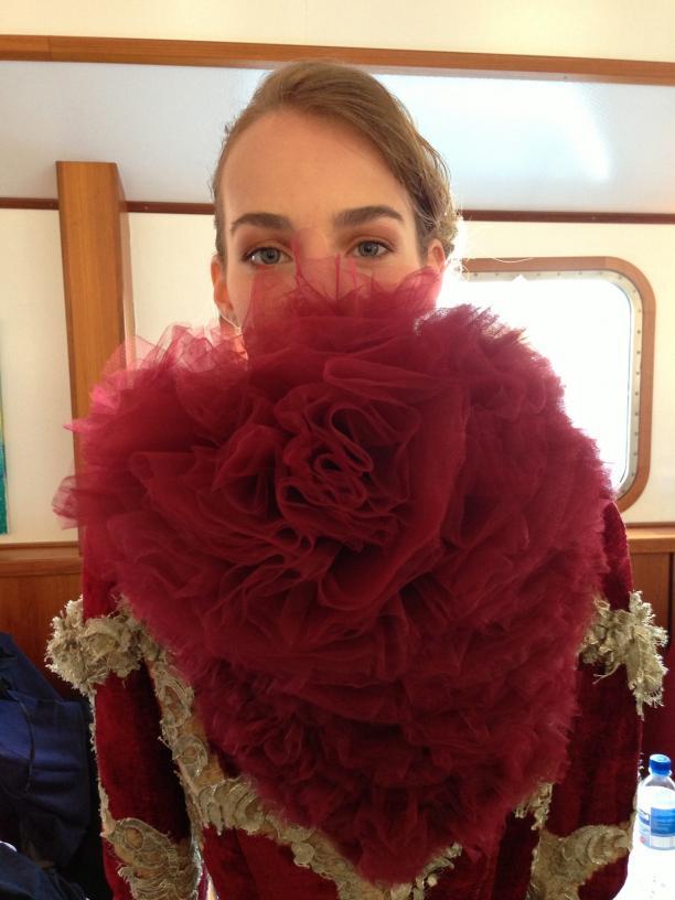 Model Maartje Verhoef kijkt nog net over de rode corsage van haar outfit heen, een laatste check voor de combinatie van make-up en kleding. Foto: ©Sanne van Gestel
