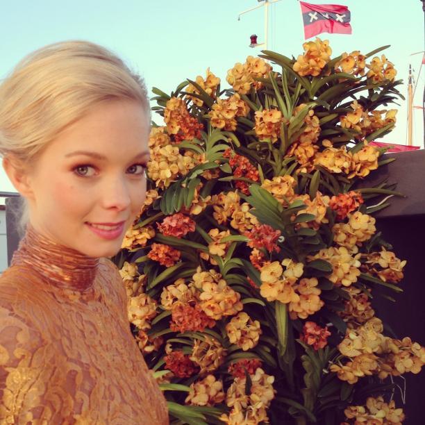 Model Esra Heijmans in een jurk van Poetic Clash tegen een achtergrond van oranje bloemen. Foto: ©Sanne van Gestel