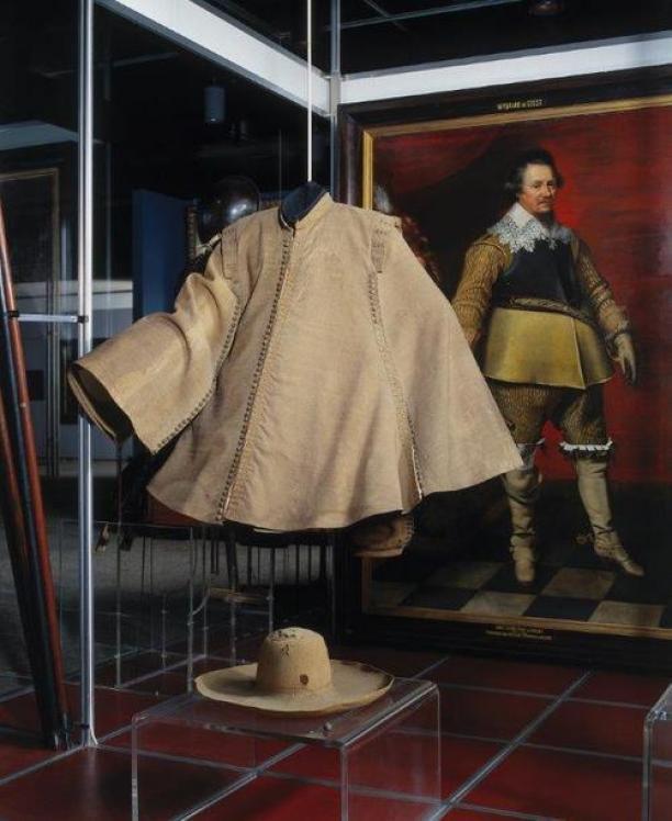 Ruitermantel op frame van polyester, bekleedt met zeemleer, met op de achtergrond het portret van Ernst Casimir, Rijksmuseum Amsterdam.