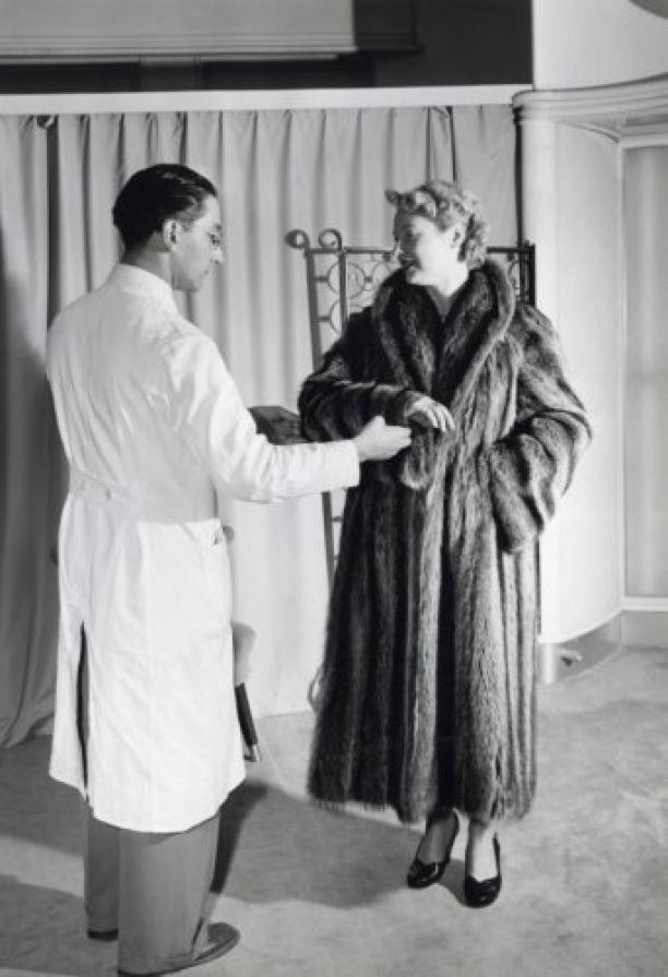 Een vrouw [in bontwinkel] bezig met het passen van een jas. De bontcoupeur inspecteert de bontjas / bontmantel van de cliënte. De jas bestaat uit 34 wasbeerhuidjes. Nederland, Amsterdam, 21 augustus 1953. Foto: Wout van de Hoef.