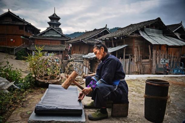 Een Dong vrouw kalandert een doek, die eerst met indigo is geverfd, Si Zhai, Liping Country. Foto Wu Zeng Ou. Via: Museum Rijkswijk.