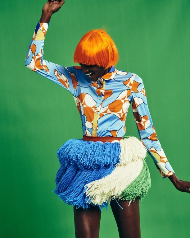 Portret van dansende donkere vrouw in fel gekleurde kleding
