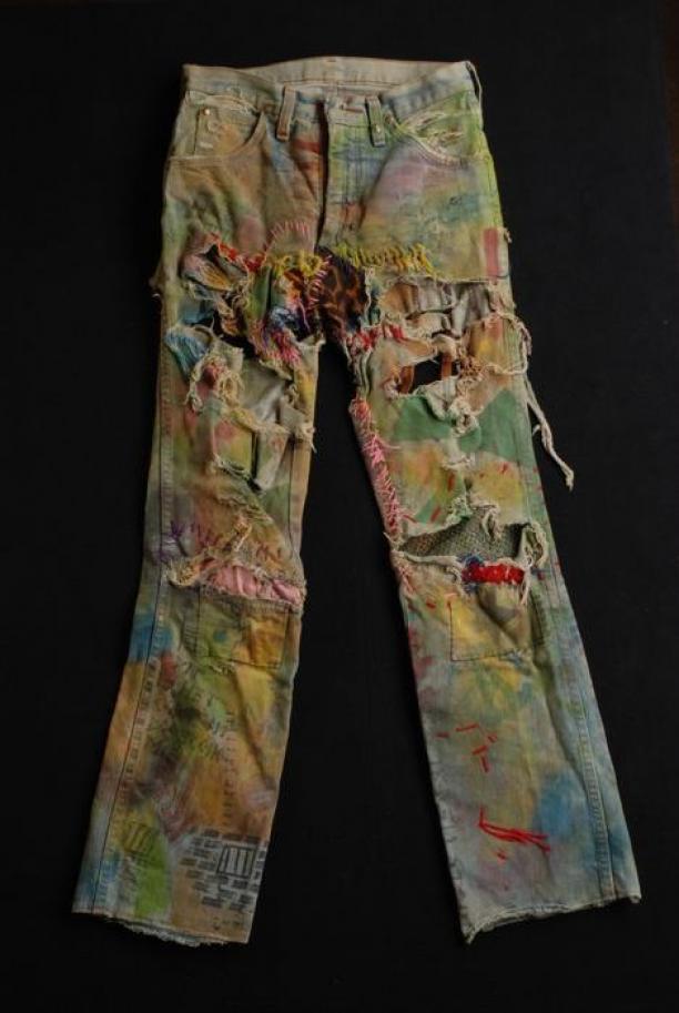 "Afb. 2 Jeans, ""Wrangler"", gescheurd, beschilderd, beschreven en met verschillende stoffen bewerkt, punkkleding, 1981, collectie Museum Rotterdam nr. 24341-2."