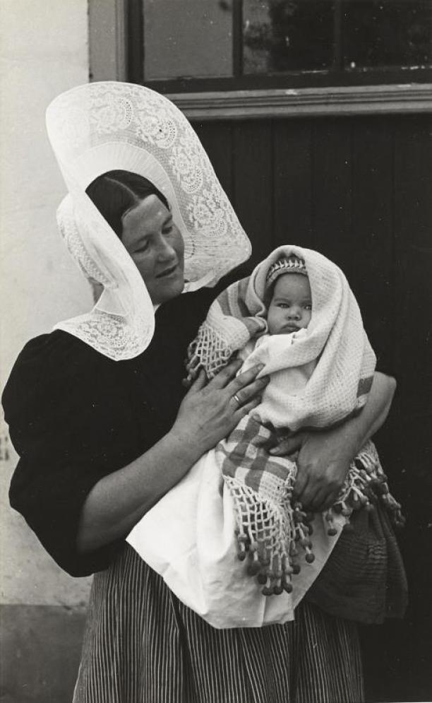 Vrouw met ingebakerde baby in streekdracht uit Huizen, 1945, collectie Nederlands Openluchtmuseum.