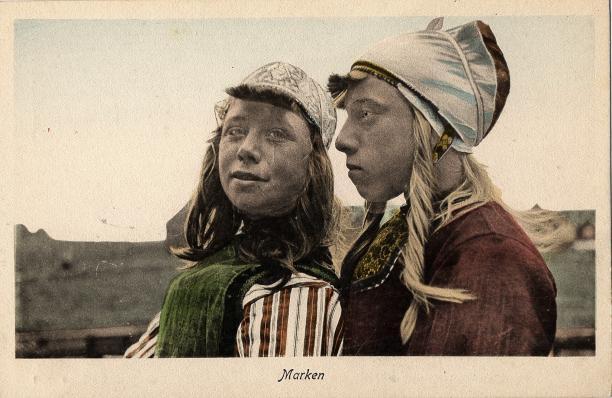 Afb.1 Twee meisjes in Marker streekdracht. Het rechter meisje is in zware rouw. Ingekleurde ansichtkaart uit de collectie van het Nederlands Openluchtmuseum (N.11979)