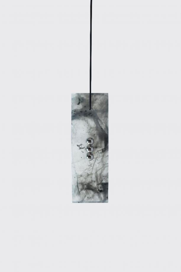 Een hanger van gemêleerd grijze jade verticaal doorboort met drie zilveren piercings hangend aan een zwarte rubberen ketting.