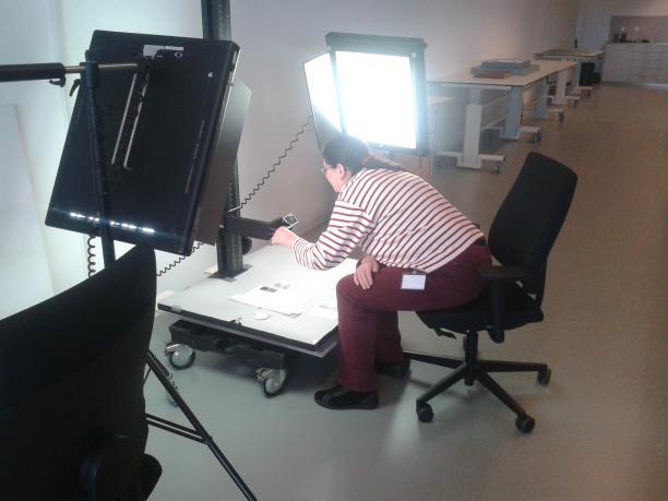 Textielvrijwilliger Anneke Jesse tijdens het fotograferen van de miniaturen.