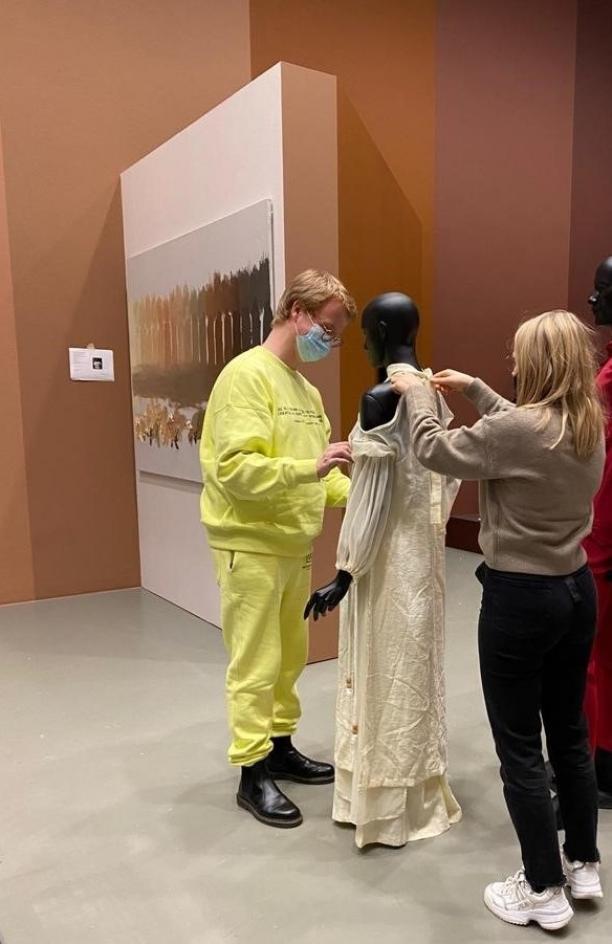 Foto van twee mensen die een mannequin aankleden in een museumzaal.