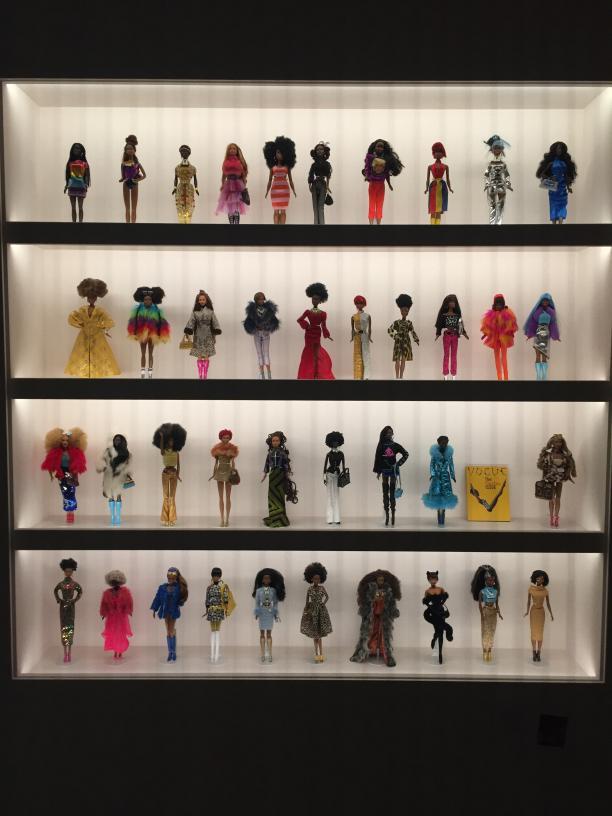 Foto van wandpaneel met planken met daarop verschillende Barbie poppen.