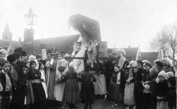 afb. 3 Onbekend, Hanicotte verkleed als Sinterklaas, wordt in een draagstoel naar Hotel Spaander gebracht, foto, waarschijnlijk 1898, coll. ZZM F0045226.; Zuiderzeemuseum, 'Zee vol verhalen', 1880-1932, Zuiderzeegebied, Volendam, Sinterklaas, Hanicotte