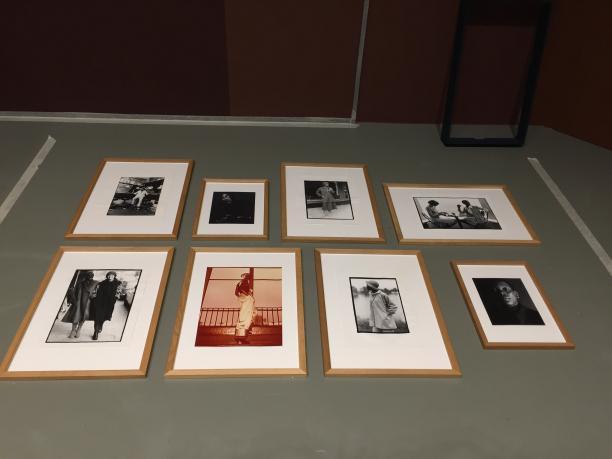 Foto. Op de vloer liggen 2 rijen van 4 zwart-en-wit foto's ingelijst.
