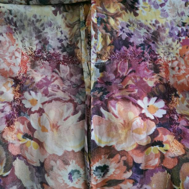 Blog Modemuze Birthe Weijkamp Hoe ga je om met vintage. Afb. 4 Door het gebruik van verschillende kleuren borduurgaren is een grote winkelhaak in de rok van een gebloemde japon nagenoeg onzichtbaar hersteld, binnen en buitenkant