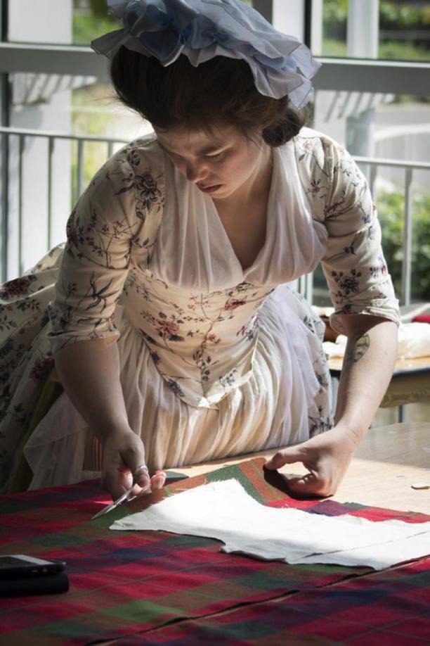 Abby aan het werk. Hier knipt ze de stof voor de voorpanden, naar voorbeeld van de linnen voering, die eerder al op het model gepast en geknipt is.