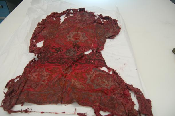 Rechthoekige rode lap met Oosterse borduurmotieven.