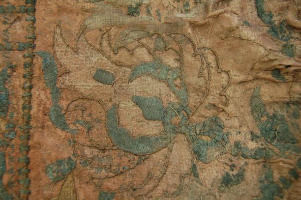 Detail van een bloemmotief o.a. gemaakt van applicaties van zilverdraad, nu gecorrodeerd en zwart.