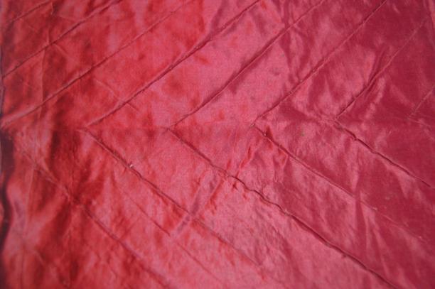 Detail van één van de fragmenten van rood satijn met zigzagmotief, de hoge glans is nog goed zichtbaar.
