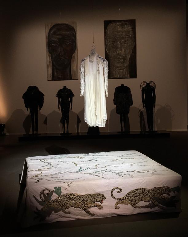 De de communiejurk van Cleo Vissers-Brun op de Dutch Fashion Heritage tentoonstelling, ontworpen door Berry Brun. Het hangt boven de lederen Fong Leng-beddensprei. Daarachter enkele ontwerpen van Mart Visser. Foto: Cleo Vissers-Brun.