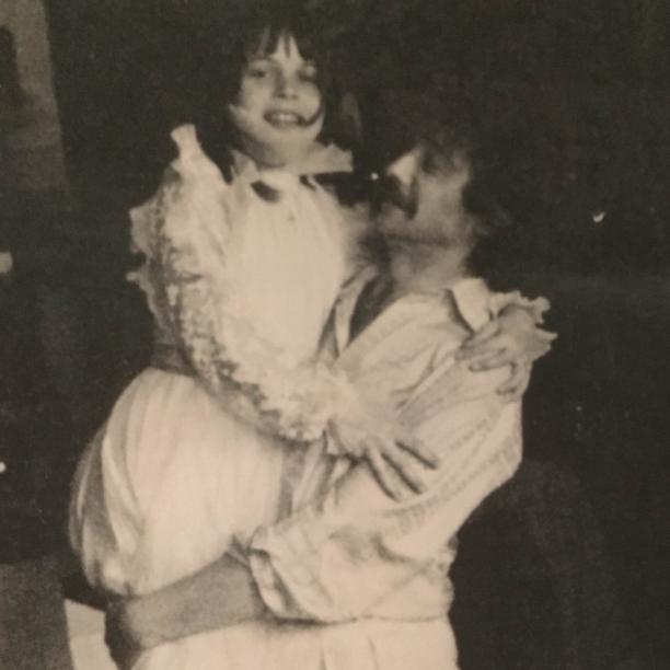 Cleo Vissers-Brun in haar communiejurk in de armen van haar oom Berry.