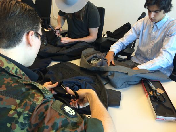 Studenten knippen en scheuren de tweedehands colberts die zijn meegebracht door Adam voor nader onderzoek.
