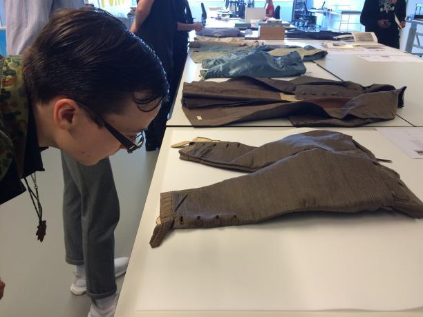 Een student bekijkt het kledingstuk van dichtbij