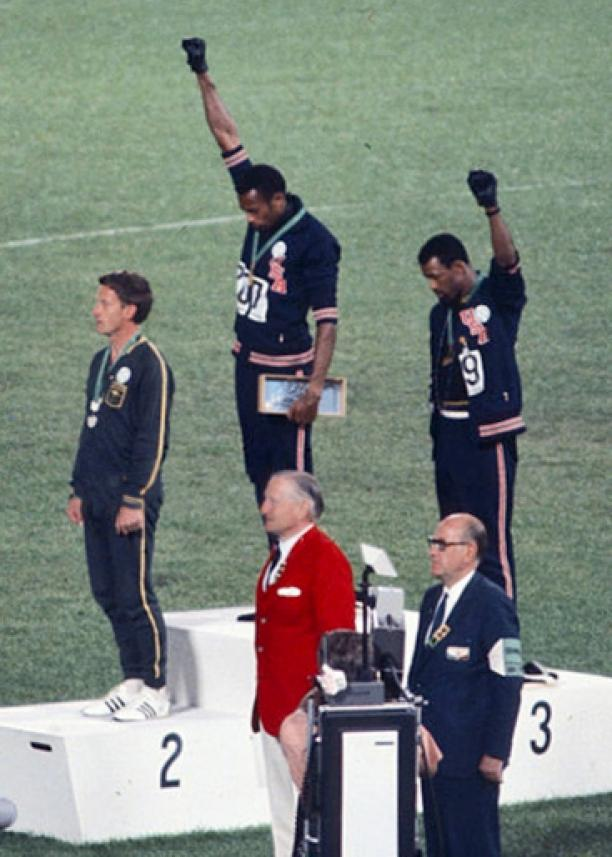 Medaillewinnaars Tommie Smith (goud), Peter Norman (zilver) en John Carlos (brons) staan op het podium van de Olympische Spelen, 1968. Smith en Carlos houden een gebalde vuist in de lucht als mensenrechten- of Black Power-saluut. Bron: Wikipedia.