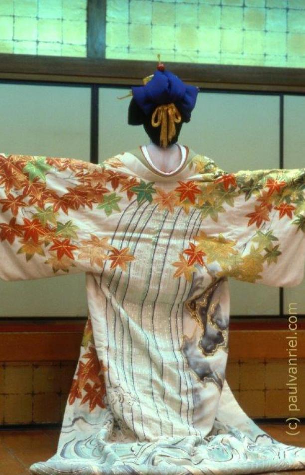 Afb. 6: De pose tijdens de dansshow van deze geisha laat haar herfstkimono, met esdoornblad decoratie in oranje, geel en groen, mooi zien. Foto: Paul van Riel, geisha show in Tokyo 1986