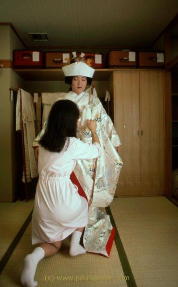 Afb. 4: Bruid wordt gekleed in traditionele stijl. De bruidskimono is een overblijfsel uit de middeleeuwse samoeraikleding, net als het korte zwaard met kwast dat ze onder haar kleding draagt. Foto: Paul van Riel, Happo En Wedding Garden, Tokyo 1984