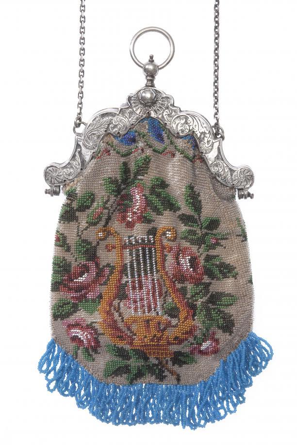 Kralentas met zilveren beugel. De kralentas is 19de eeuws uit Duitsland, de zilveren beugel komt uit de 18de eeuw uit Amsterdam (1717, vervaardiger Van Wijk).
