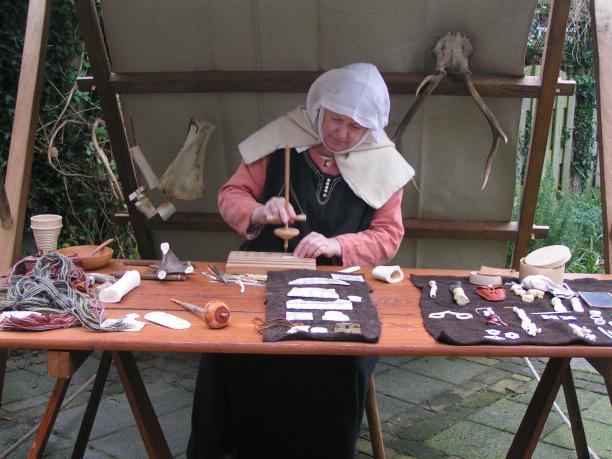 Hier zie je Marloes in een middeleeuwse kraam tijdens een demonstratie over been bewerken. Fotografie Hein Bakker.; Beleeft het verleden, Verborgen dracht in schijnwerpers, benenkam, kam, ivoor, koeienbot, hondenbot, replica, namaken, reenactment