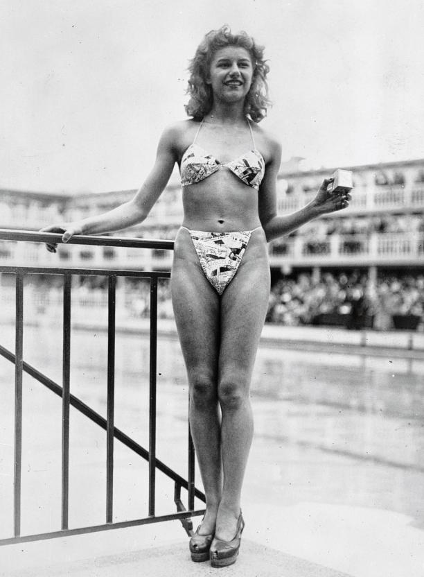 Resist! Modemuze Marit Eisses. Micheline Bernardini in bikini met krantenprint en in haar hand het doosje waar de bikini in past. 7 juli 1946, collectie Hulton Archive, Getty Images