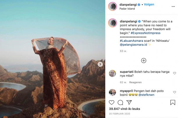 vrouw met wapperende sjaal en jurk op de top van een berg