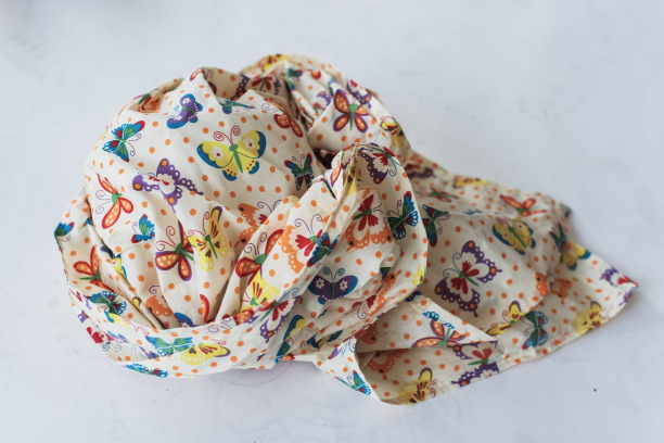 hoofddoek met kleurrijk patroon met stippen en vlinders