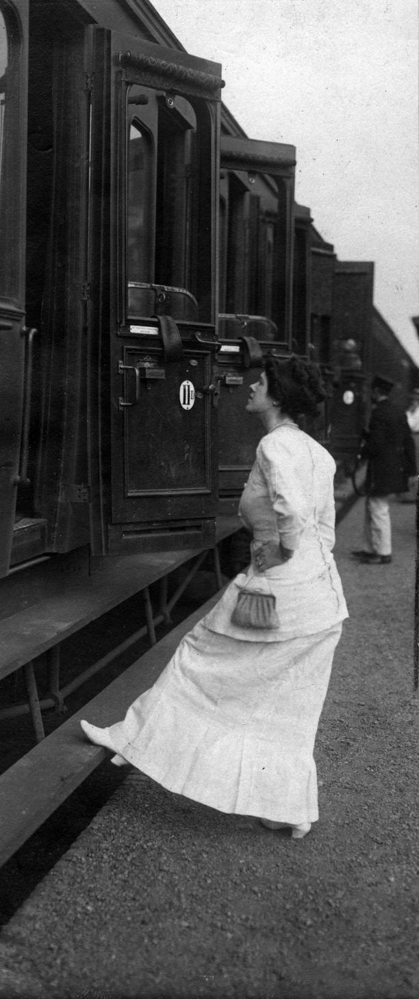 Vrouw in witte jurk neemt afscheid van iemand in de trein, met haar voet op de 'treeplank', en haar hand (met daaraan een klein tasje) in haar zij.