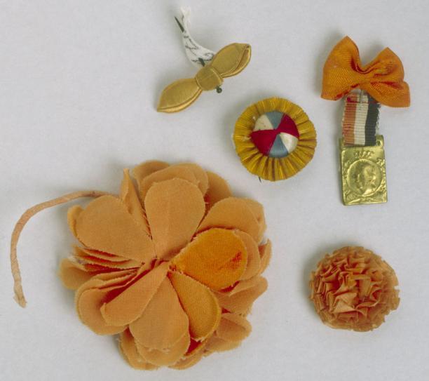 Twee oranje rozetten waarvan 1 met een rood, wit en blauw gestreepte knoop, een speld met een oranje strik, een speld met een metalen hanger met een afbeelding van koningin Wilhelmina en een oranje corsage.