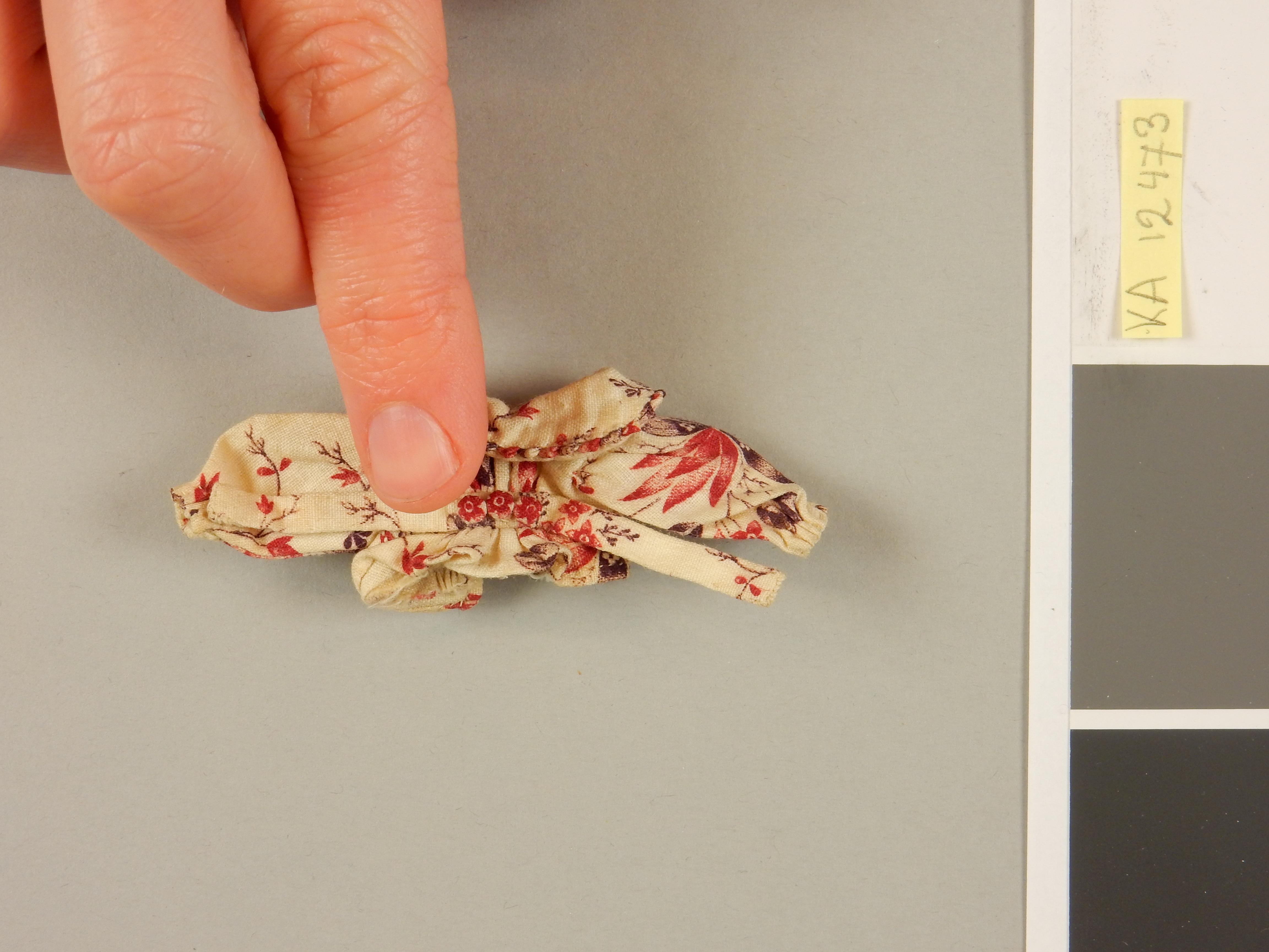 Bovenkleding in miniatuur. De vinger geeft de schaal van het kledingstuk aan. Foto: Judith van Amelsvoort.